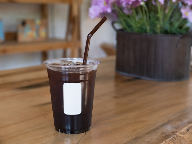 Ijs zwarte koffie op houten tafel in het café