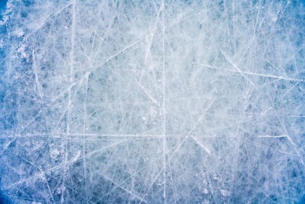 Ijsachtergrond met tekens van het schaatsen en hockey, blauwe textuur van pisteoppervlakte met krassen