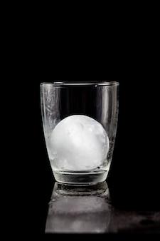 Ijsbal in cocktailglas op een reflecterende zwarte tafel.