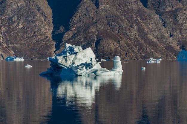 Ijsberg in groenland fjord met reflectie in kalm water. zonnig weer. gouden uur.