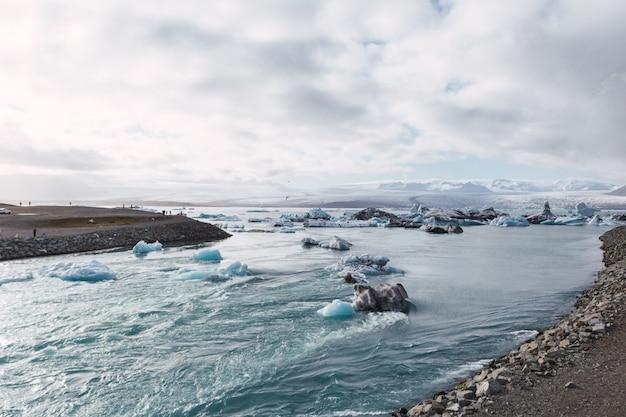 Ijsbergen in de gletsjermeer van ijsland bij zonsondergang