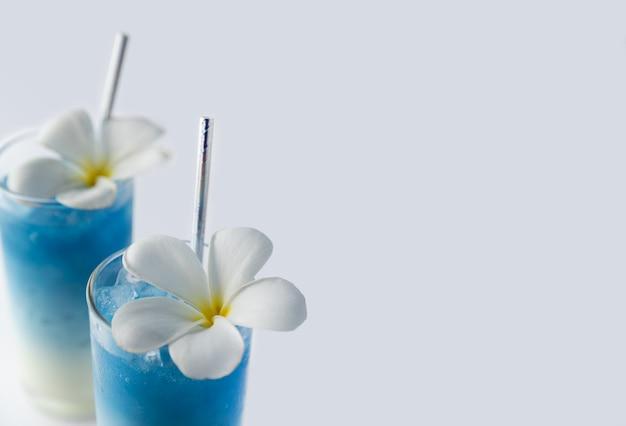 Ijsblauwe vlinder erwt latte drankjes met tropische bloemen decor. gezonde thaise traditionele cocktails in glazen