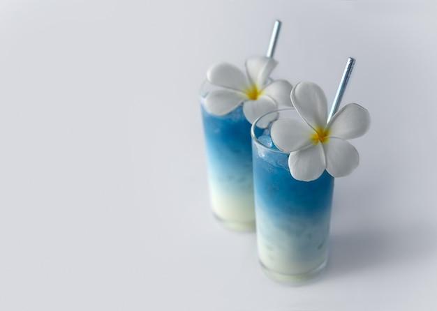 Ijsblauwe vlinder erwten drankjes met tropische bloemen decor. gezonde thaise traditionele cocktails in glazen