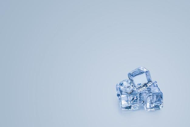 Ijsblokjes die over een blauwe achtergrond worden geïsoleerd