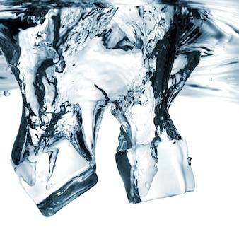 Ijsblokjes in het water gevallen met splash geïsoleerd op wit