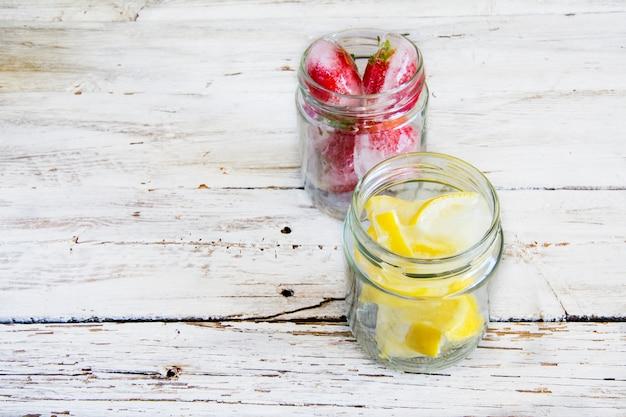 Ijsblokjes met citroenen en bevroren aardbeien