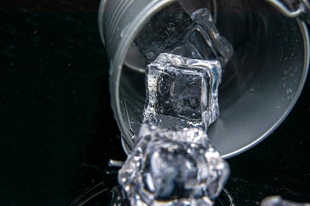Ijsblokjes met een druppels water in backet op de zwarte tafel