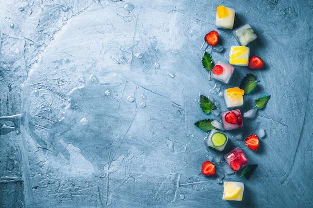 Ijsblokjes met fruit en gebroken ijs op een steenblauwe ondergrond met muntblaadjes en vers fruit. munt, aardbei, kers, citroen, sinaasappel. plat lag, bovenaanzicht