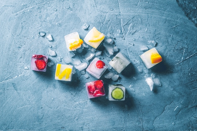 Ijsblokjes met fruit en gebroken ijs op een steenblauwe ondergrond. munt, aardbei, kers, citroen, sinaasappel. plat lag, bovenaanzicht