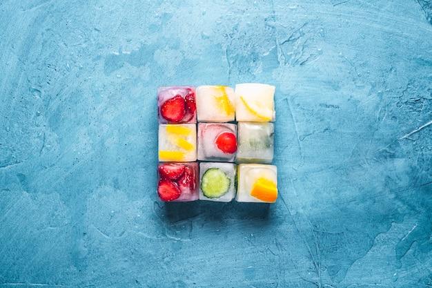 Ijsblokjes met fruit op een steen blauwe ondergrond. de vorm van het vierkant. munt, aardbei, kers, citroen, sinaasappel. plat lag, bovenaanzicht