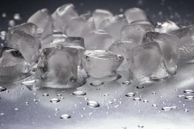 Ijsblokjes op een reflecterende tafel met druppels water