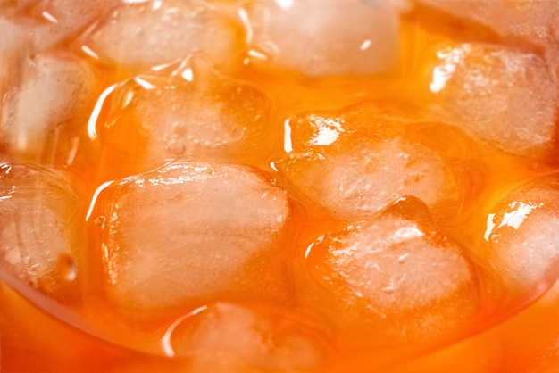 Ijsblokjes smelten in glas met aperol spriz cocktail, close-up