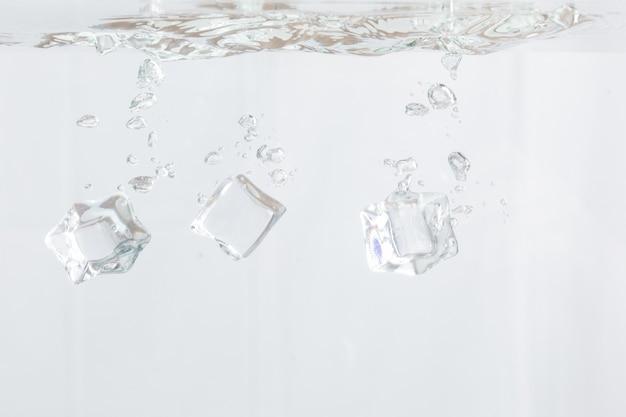 Ijsblokjes vallen in water op witte achtergrond