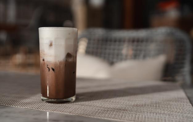 Ijschocolade of cacao latte in glas op tafel met ochtendlicht, verfrissend koud drankje