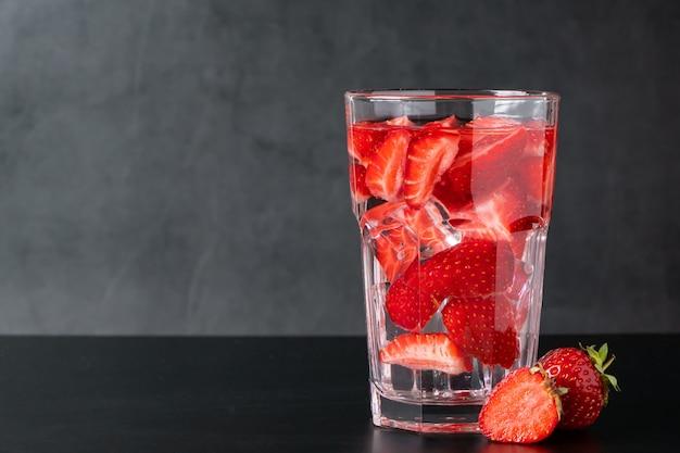 Ijsdrank met aardbeien op een zwarte achtergrond. zomerse bessenlimonade. plaats voor tekst.