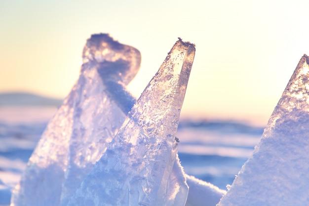 Ijsheuveltjes op het baikalmeer. transparante blauwe ijsschotsen bij zonsondergang. winter tijd