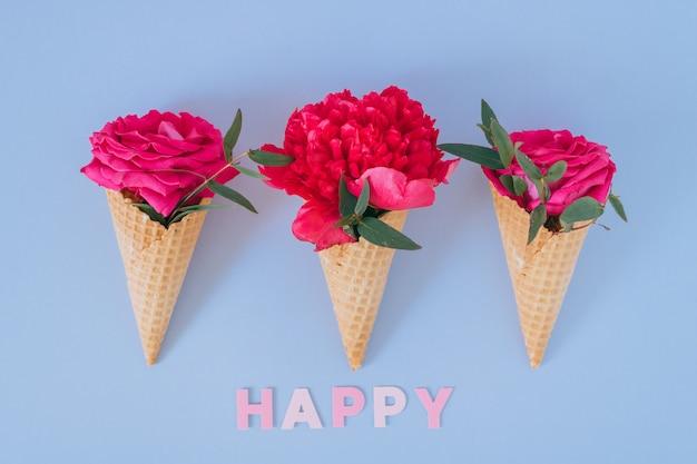 Ijshoorntjes met roze pioen en rozen op blauwe, platte laag. vrolijke tekst