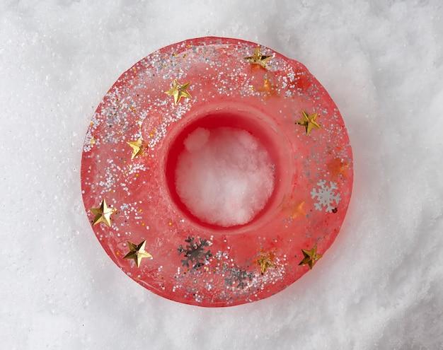 Ijskandelaar met glitters op verse sneeuw