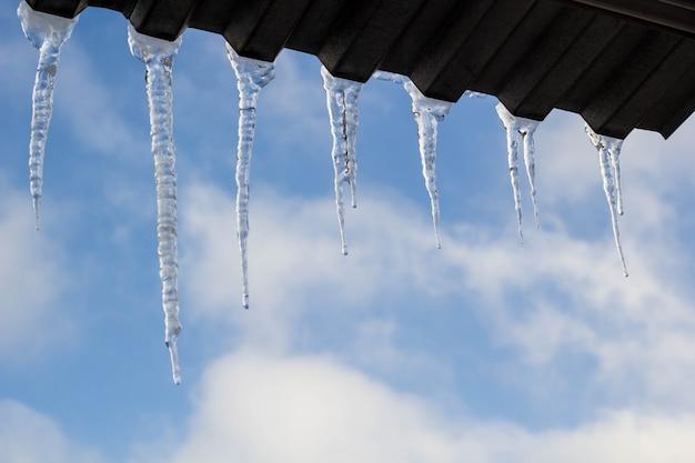 Ijskegels die op dak bij de winter hangen. natuurlijke ijsvorming van ijskristallen die op dakrand bij de winter hangen