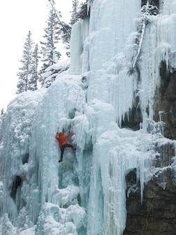 Ijsklimmer op bevroren waterval, johnston-canion, het nationale park van banff, alberta, canada
