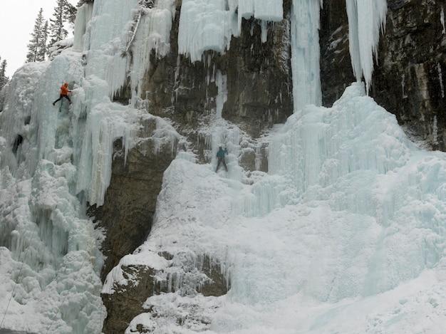 Ijsklimmers op bevroren waterval, johnston-canion, het nationale park van banff, alberta, canada