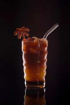 Ijskoffie in een glas op zwarte achtergrond. koude koffiedrank of cocktail met ijs op een donkere achtergrond