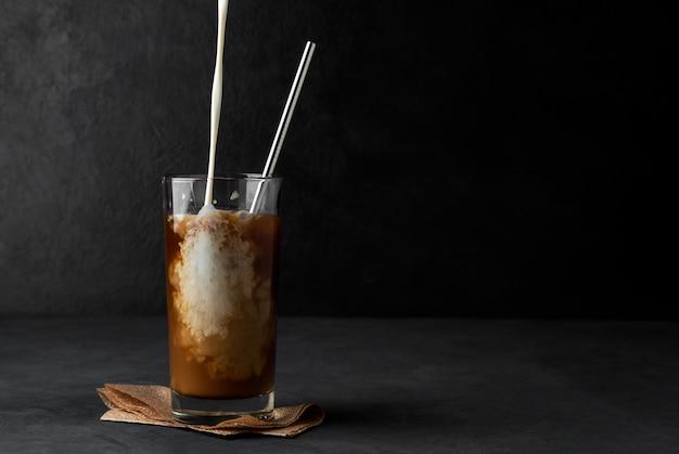Ijskoffie met gietroom in een glazen beker met een metalen rietje op een donkere ruimte