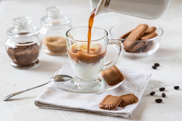 Ijskoffie met melk, chocoladesiroop en koekjes.