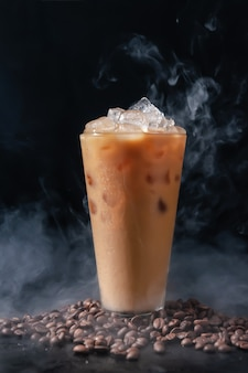 Ijskoffie met melk in hoog glas en koffiebonen op donkere achtergrond