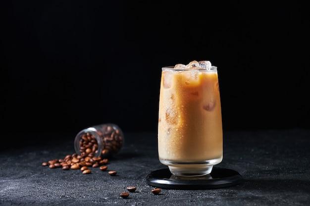Ijskoffie met melk in hoog glas op donkere achtergrond. concept verfrissend zomerdrankje.