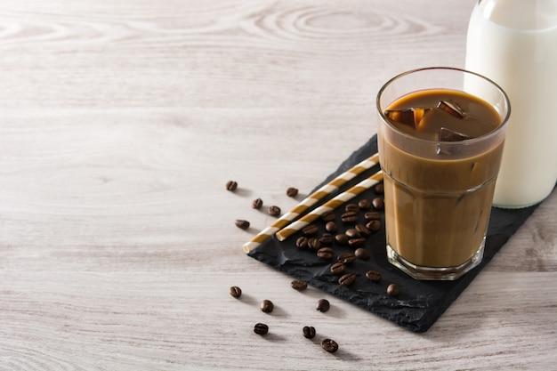 Ijskoffie of caffe latte in een hoog glas op witte houten tafel kopie ruimte
