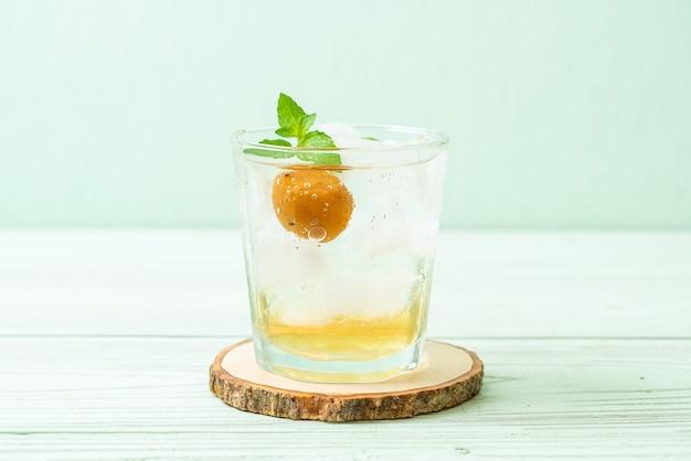 Ijskoude pruimensap met frisdrank en pepermunt op houten tafel. verfrissing drankje