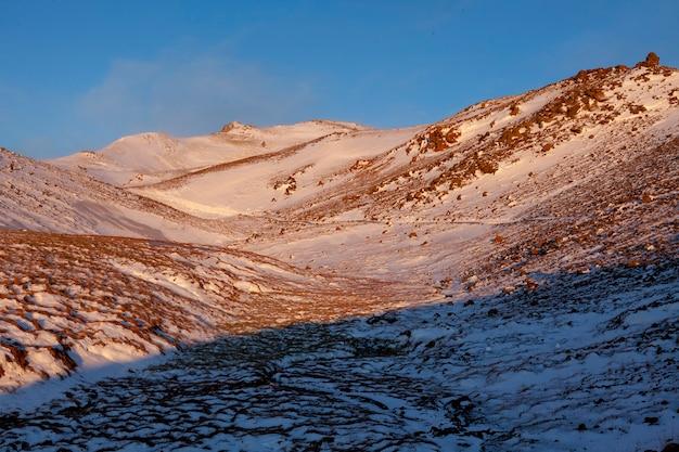 Ijsland. de stoomvallei van reykjadalur in de buurt van reykjavik, in ijsland met heuvels die in de winter wit zijn bedekt
