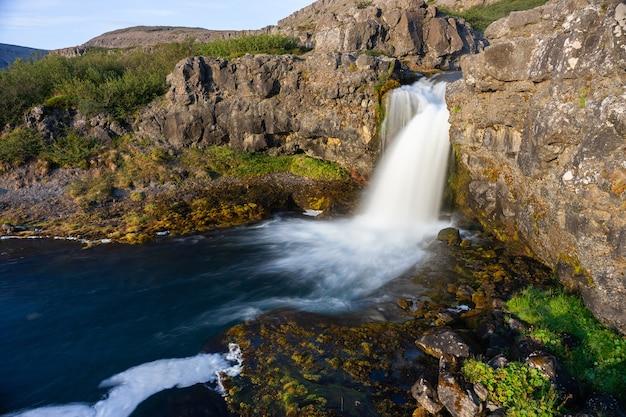 Ijsland waterval close-up weergave van de goden klif met lange belichtingstijd vloeiende beweging van water in zomer landschap.