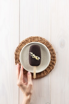 Ijslolly op een stokje in een kom op een houten tafel