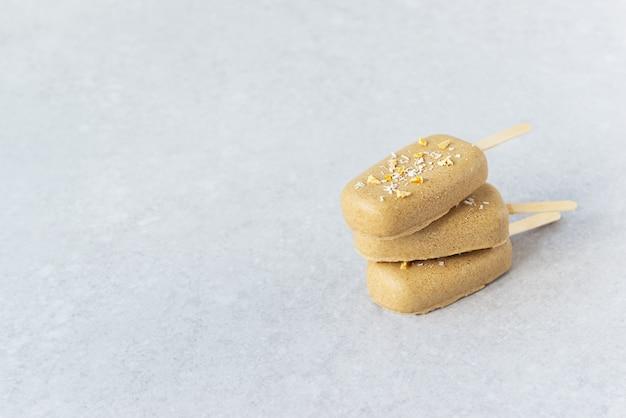 Ijslolly op een stokje met chocolade cashewnoten op een grijze achtergrond