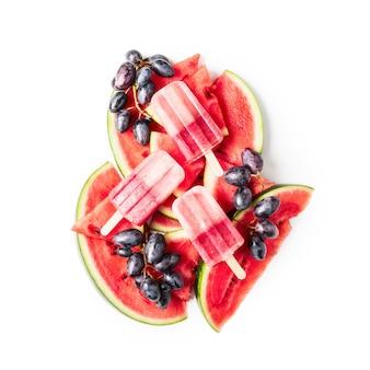 Ijslollys, gesneden watermeloen en blauwe druif fruit berry geïsoleerd op een witte achtergrond uitknippad opgenomen. bovenaanzicht, plat gelegd. ontwerpelement