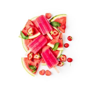 Ijslollys, gesneden watermeloen, muntblaadjes en aardbei fruit berry geïsoleerd op een witte achtergrond uitknippad opgenomen. bovenaanzicht, plat gelegd. ontwerpelement