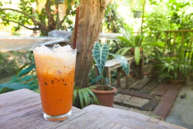 Ijsmelkthee in modern glas met uitzicht op de natuurlijke tuin, thaise drank