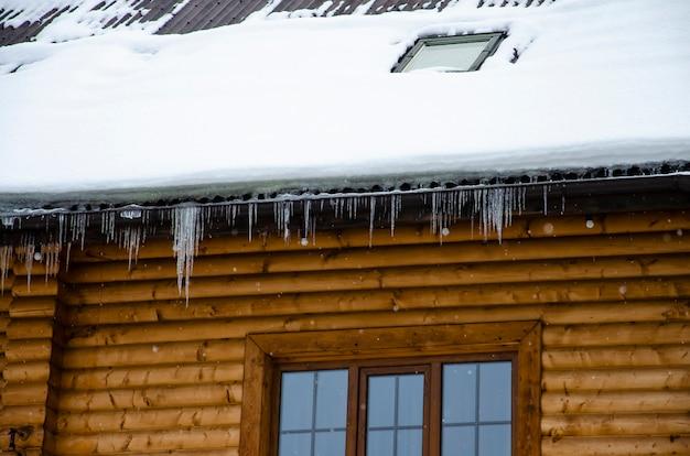 Ijspegels die op het dak van een houten huis hangen.