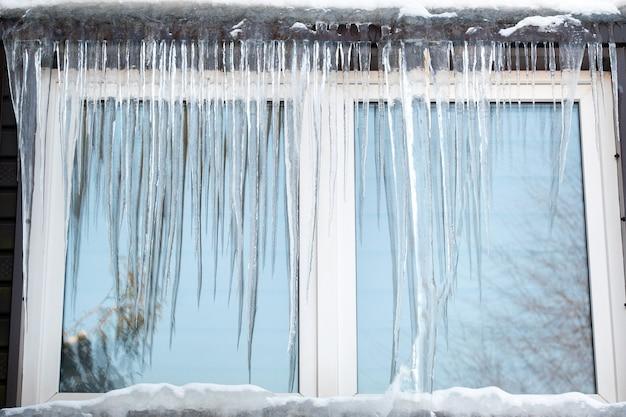 Ijspegels op het raam van het huis op een ijzige dag.