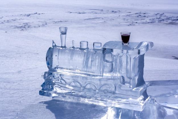 Ijssculptuur in de vorm van een treinlocomotief en rode likeur in een glas. ijs lost op in de zon. wazig sneeuw op de achtergrond. horizontaal.