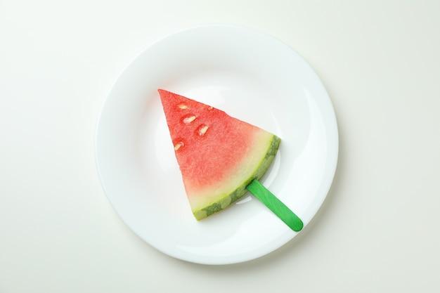 Ijsstok met watermeloenplak op plaat op witte achtergrond