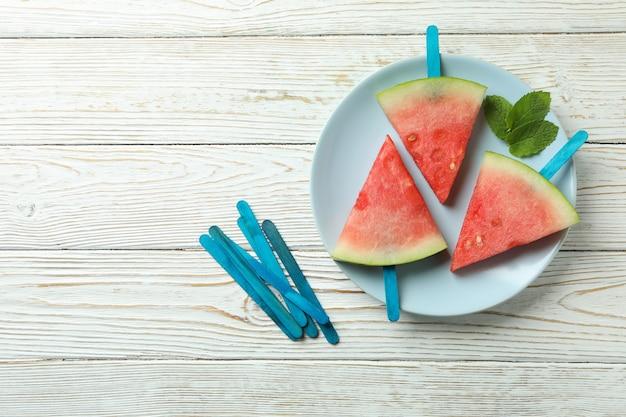 Ijsstokken met watermeloenplakken op plaat op witte houten tafel