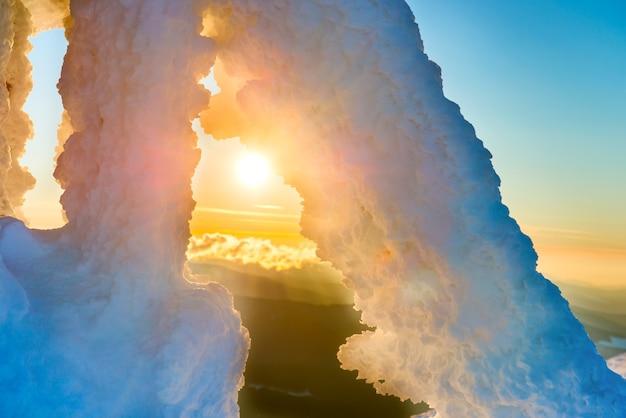 Ijsstructuur tegen dramatische zonsondergang en oranje zon