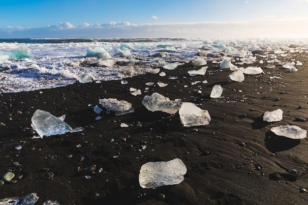 Ijsstukken op zwart zandstrand in ijsland