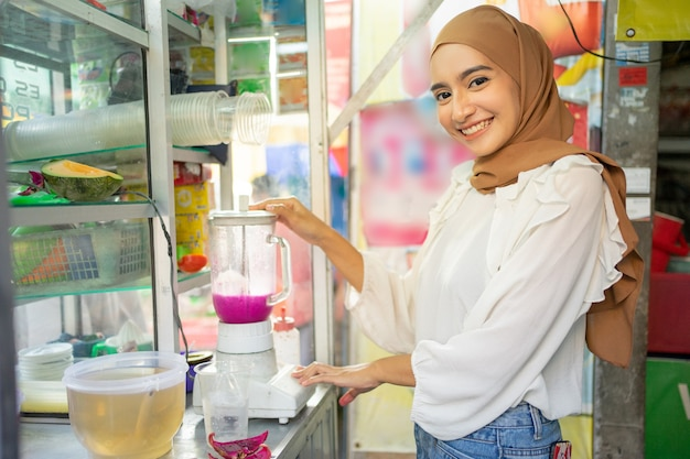 Ijsverkoper hijab meisje lacht terwijl ze blender vasthoudt