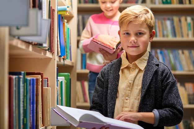 Ijverig kind jongen met boek tussen boekenkasten in campusbibliotheek, hij kijkt naar de camera.
