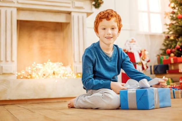 Ijverig kind. lage hoek shot van een vriendelijk ogende jongen zittend op de vloer en vrolijk lacht terwijl hij zijn prachtig ingepakt cadeau opent.