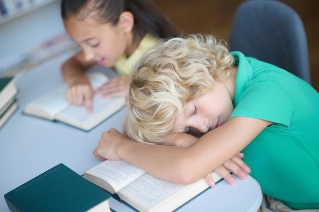 Ijverig meisje en uitgeput slaperige jongen in de bibliotheek